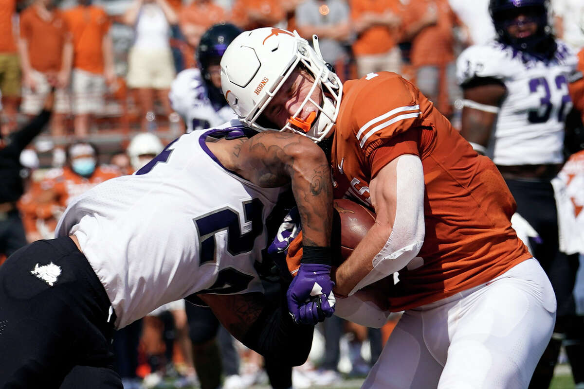 Texas wide receiver Jake Smith (7) is hit by TCU safety Ar'Darius Washington (24) as he makes a catch for a touchdown during the first half of an NCAA college football game, Saturday, Oct. 3, 2020, in Austin, Texas. (AP Photo/Eric Gay)