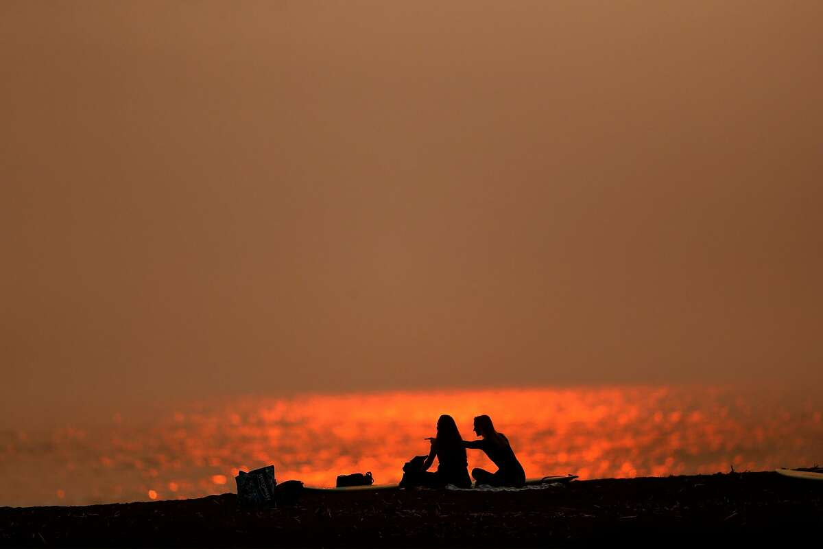 Surfers rest on the beach as the sun sets at Rodeo Beach in Sausalito on Thursday. Smoky skies prevail now, but rain is at last in the forecast.