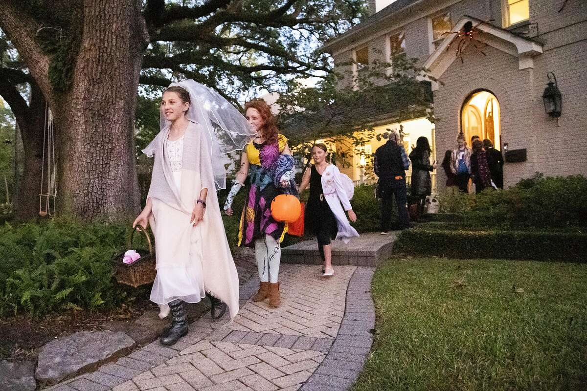 """Meredith Pryor, 12, Claire Whitehead, 13, and Anna Guerrini, 12, go trick-or-treating together in West University on Halloween, Thursday, Oct. 31, 2019, in Houston. In South Texas, Hidalgo County officials have deemed trick-or-treating """"too great a risk"""" during the coronavirus pandemic and is set to ban the annual tradition."""