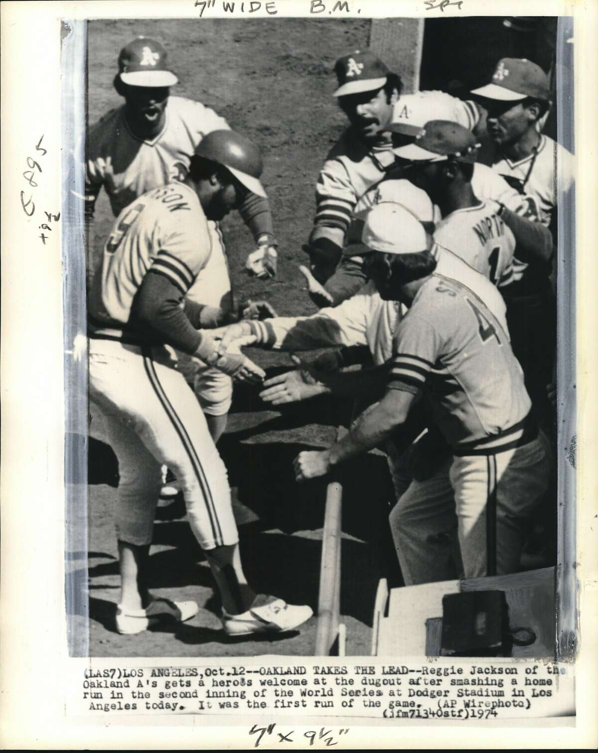 Baseball - World Series '74 (Jackson Homers). Los Angeles. Reggie Jackson of the Oakland A's gets a heroes welcome at the dugout after smashing a home run in the second inning of the World Series at Dodger Stadium in Los Angeles today. It was the first run of the game.