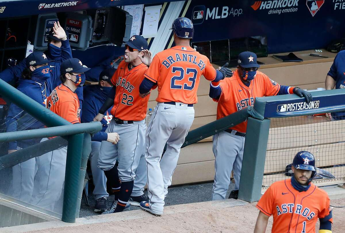 Houston Astros Michael Brantley (23) celebrates with manager Dusty Baker Jr. after he scored a run on Kyle Tucker's RBI single during the fourth inning of Game 2 of an MLB Wild Card game at Target Field, Wednesday, September 30, 2020, in Minneapolis.