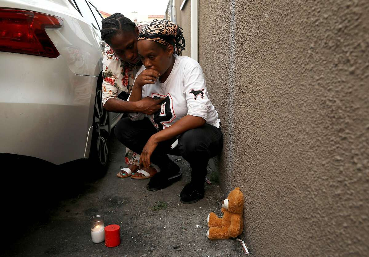 Dakota Northington (left) grieves with Dani O'Neal in the East Oakland driveway where their 16-year-old cousin, Aaron Pryor, was gunned down.