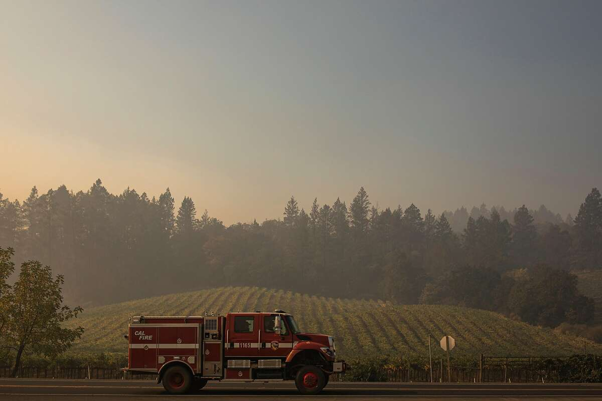 CalFire fire truck drives along St. Helena Highway passing vineyards towards the Glass Fire, Saturday, Oct. 3, 2020, in St. Helena, Calif.