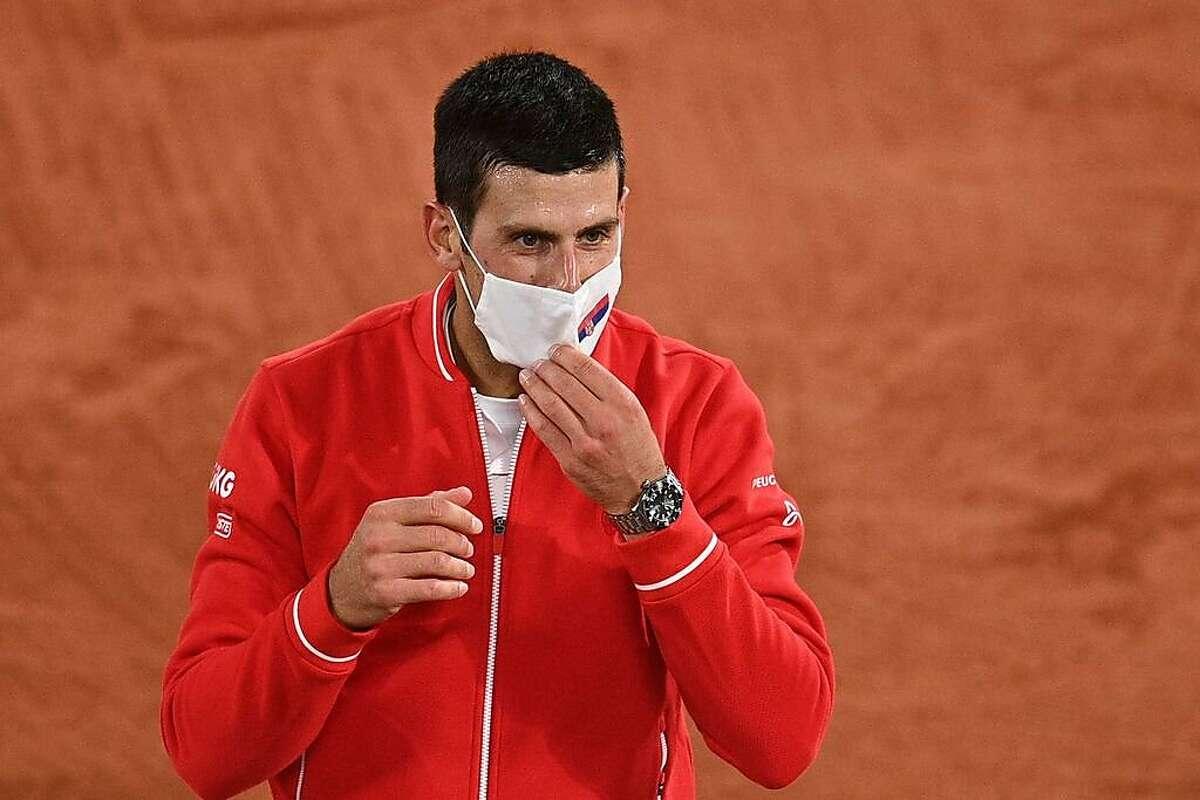 Novak Djokovic dons his mask after winning his third-round match.