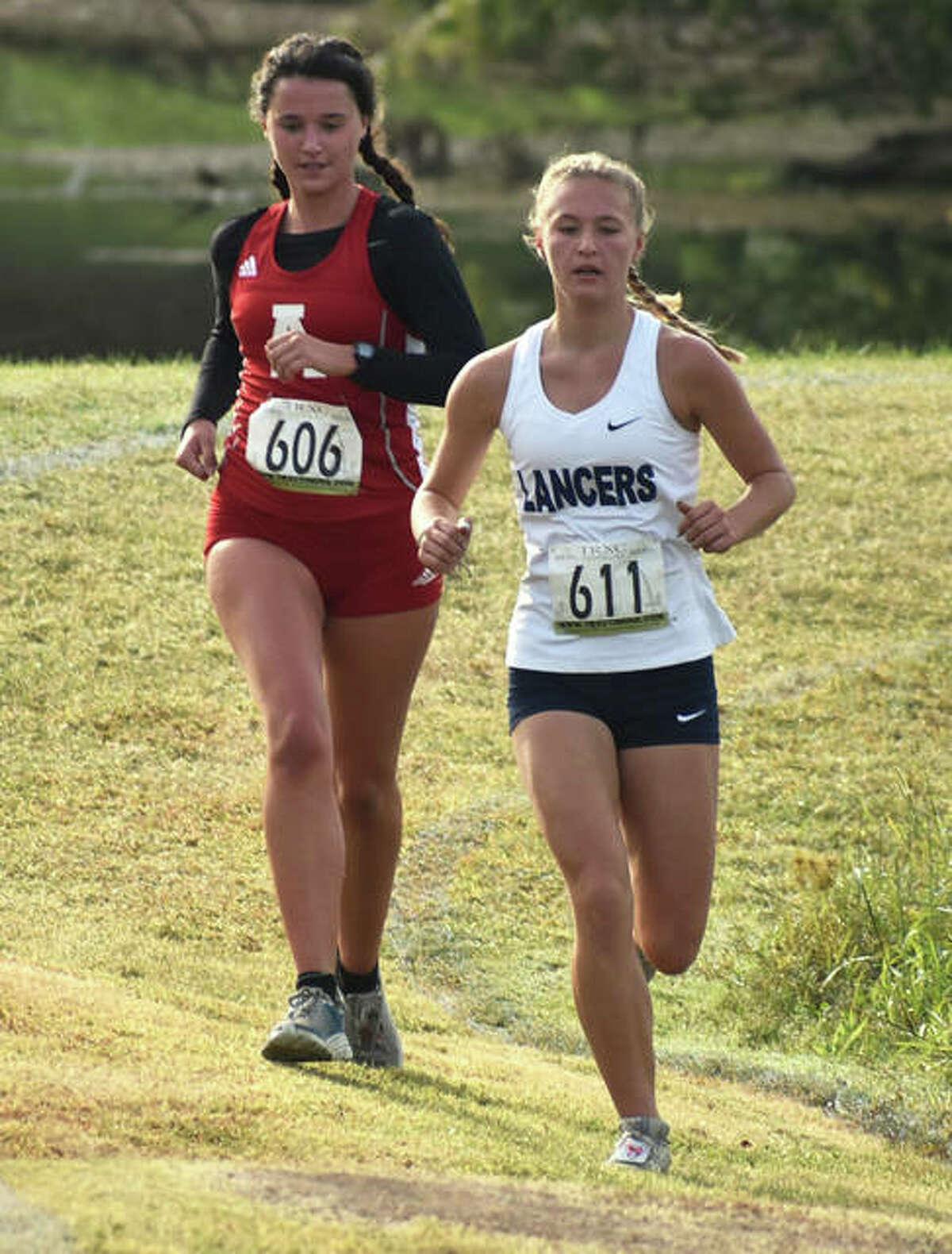 Alton's Eva Schwaab (left) runs off the shoulder of a Belleville East runner Saturday in the SWC Meet in Swansea.