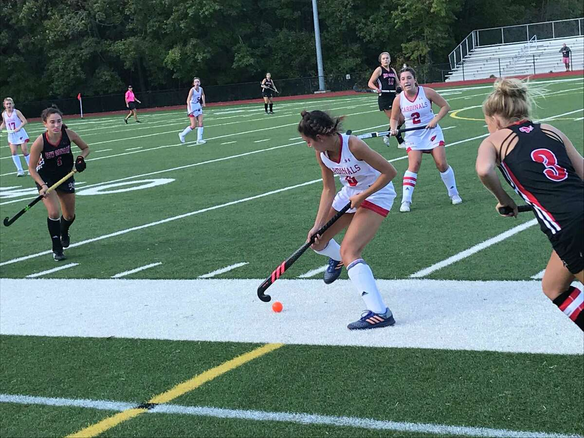 Isa Lattuada of Greenwich, center, looks to control the ball during the Cardinals' field hockey game against New Canaan on Saturday, October 3, 2020, in Greenwich, Connecticut.
