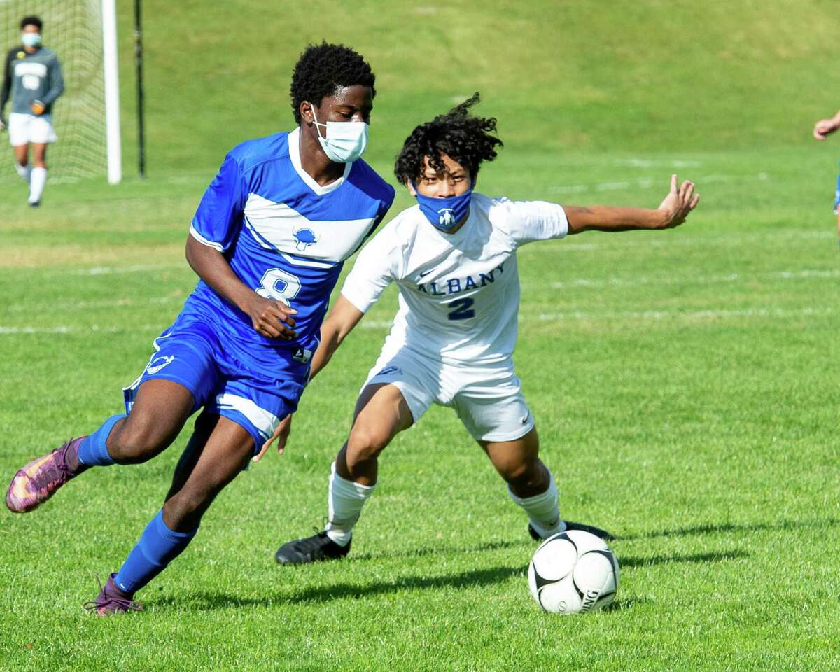 Shaker High midfielder Jaaziel Olayinka battles with Albany High defender David Ceu during a Suburban Council matchup at Shaker High School on Saturday, Oct. 3, 2020 (Jim Franco/special to the Times Union.)