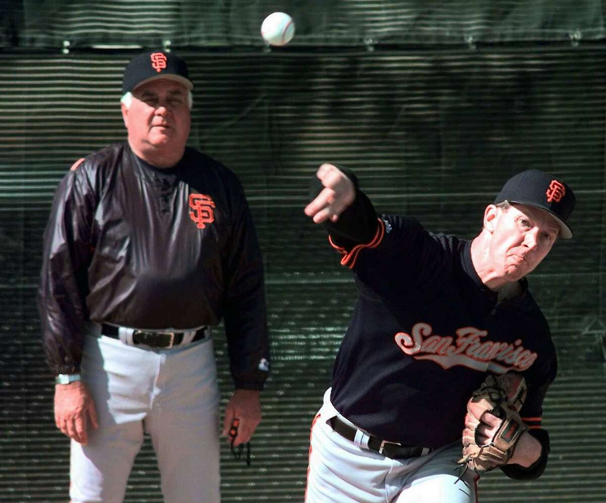 San Francisco Giants new pitcher Orel Hershiser throws as pitching coach Ron Perranoski, left, looks on during spring training workouts in Scottsdale, Ariz., Monday Feb. 23, 1998.(AP Photo/Eric Risberg)