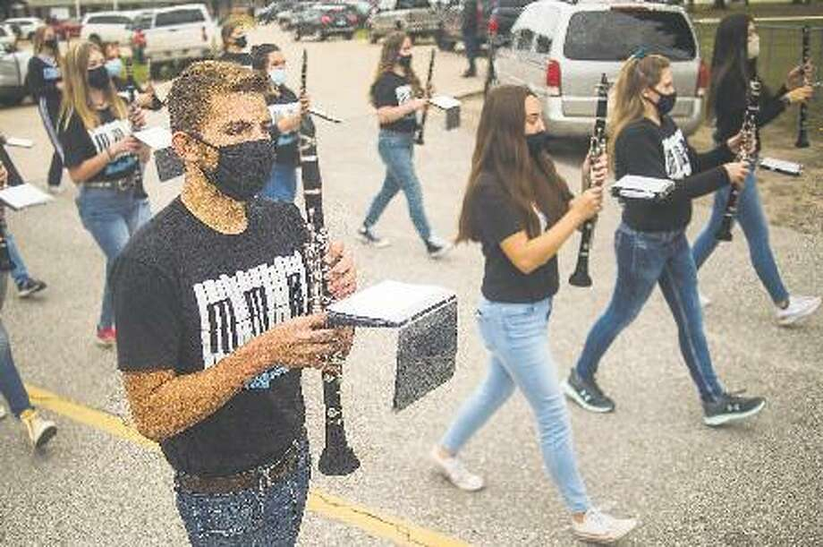 Members of the Meridian Early College High School marching band exit the field after performing ahead of a varsity football game Friday, Oct. 2, 2020 at the school. Photo: Katy Kildee/kkildee@mdn.net
