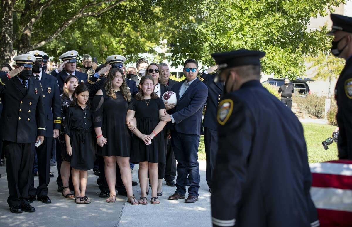 Houston Fire Department Capt. Tommy Searcy's three daughters, family, friends and colleagues, watch as his casket is carried into Champion Forest Baptist Church for his funeral service Sept. 16, in Houston. Searcy died of COVID-19.