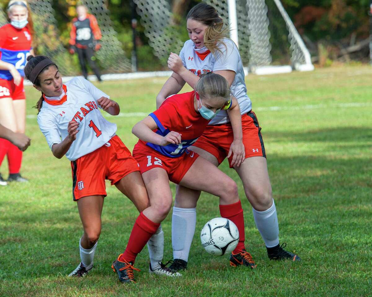 Maple Hill and Taconic Hills compete in girls' soccer earlier this season. Because of the vagueness of the mask rule, all the players are in compliance, though not all are wearing masks over their face. (Jim Franco / Special to the Times Union)
