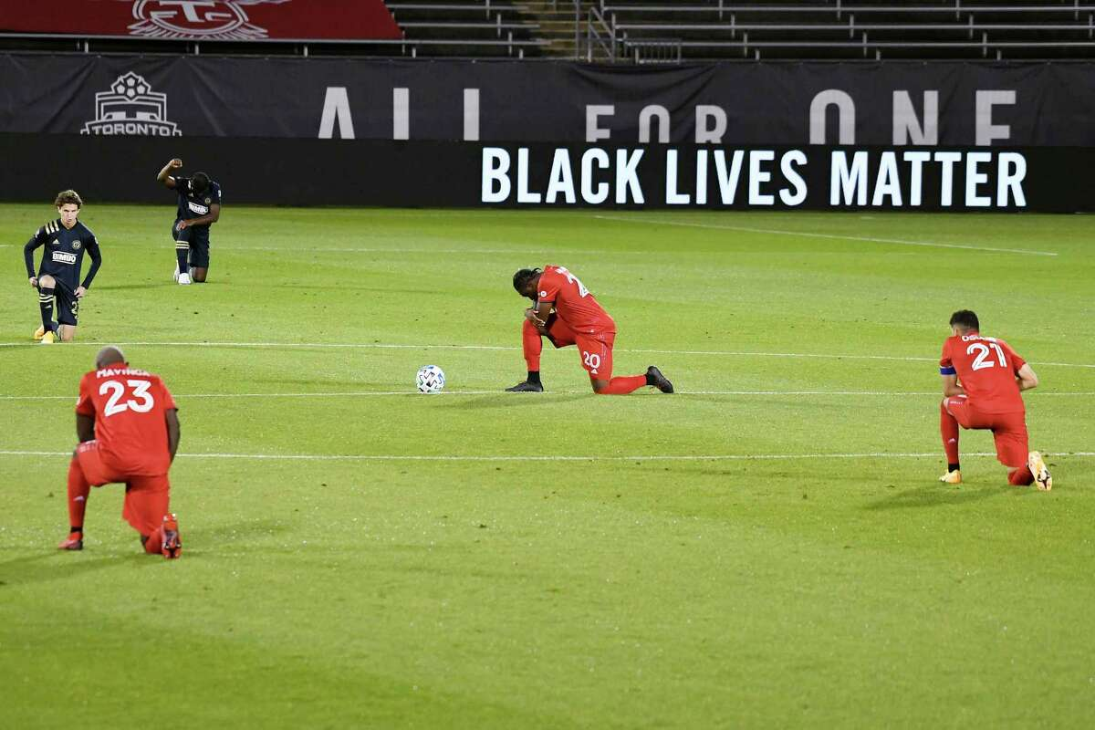 Philadelphia Union and Toronto FC players kneel at the start of Saturday's MLS soccer match in East Hartford.