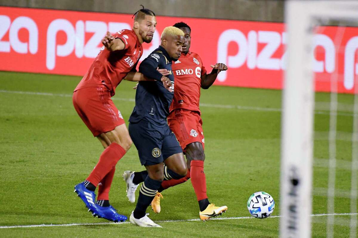 Philadelphia Union's Sergio Santos, center, cuts between Toronto FC's Omar Gonzalez, left, and Richie Laryea to score during the first half Saturday in East Hartford.
