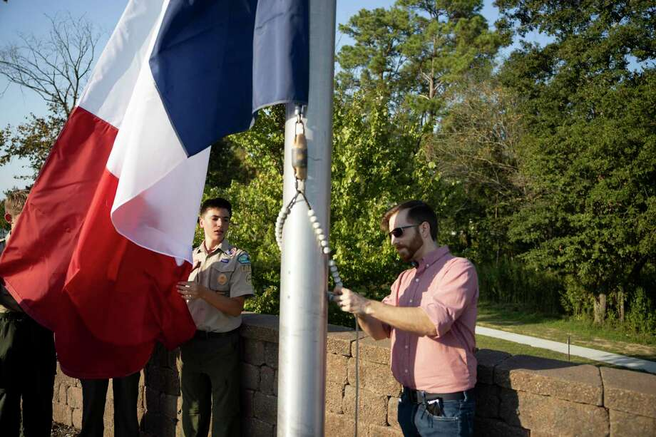 Kaden Hunter, left and his father Michael, raise a flag in memory of Cameron W. Bammel during the 10th annual Flag Replacement Ceremony on Saturday at The Lone Star Monument and Historical Flag Park. Bammel was a board member for Friends of the Flag, which oversees the park. Photo: Gustavo Huerta, Houston Chronicle / Staff Photographer / 2020 © Houston Chronicle
