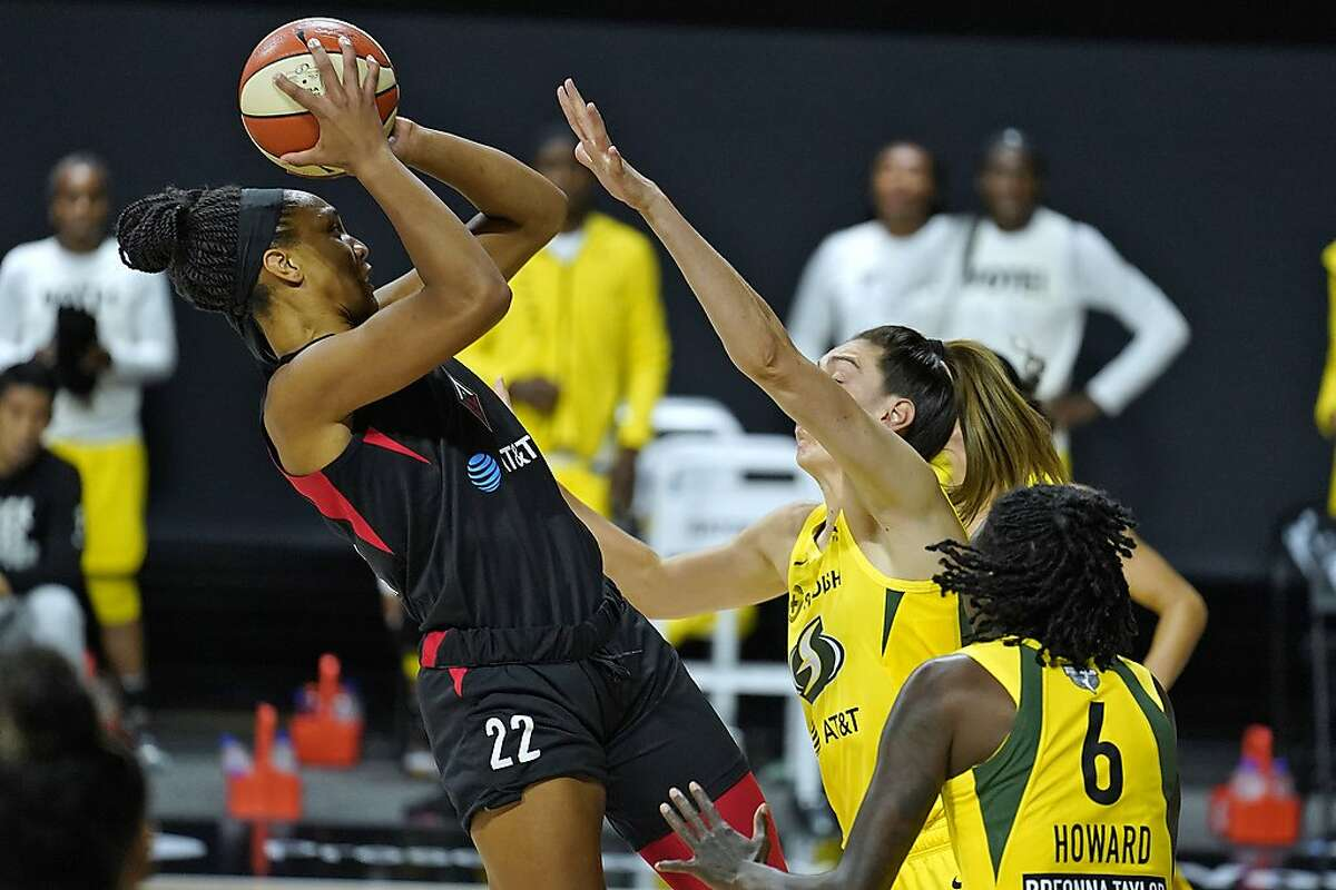 Las Vegas Aces center A'ja Wilson (22) shoots over Seattle Storm forward Breanna Stewart (30) and forward Natasha Howard (6) during the first half of Game 1 of basketball's WNBA Finals on Friday, Oct. 2, 2020, in Bradenton, Fla.