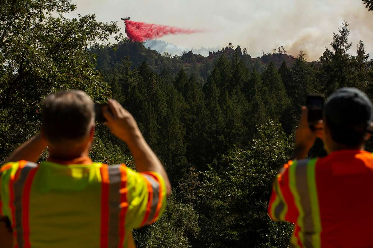 A PG&E crew watch as firefighting aircraft release fire retardant in an attempt to prevent the Glass Fire from burning towards Highway 29, Saturday, Oct. 3, 2020, in Calistoga, Calif.