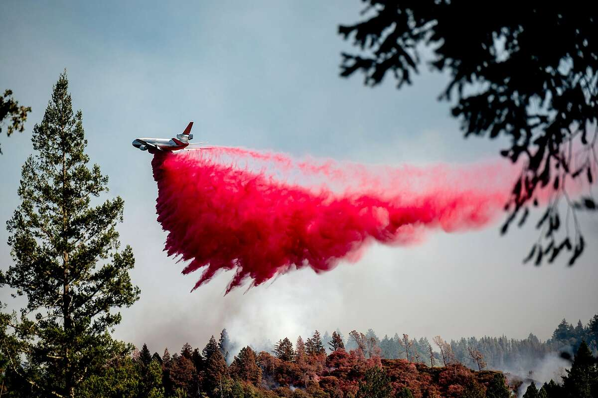 An air tanker drops retardant on the Glass Fire near Middletown in Napa County. The record-smashing blaze is just over 50% contained.