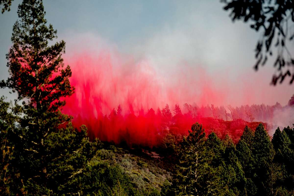 Retardant falls from an air tanker as the Glass Fire burns in unincorporated Napa County, Calif., south of Middletown on Saturday, Oct. 3, 2020.