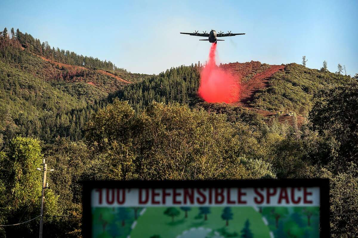 An air tanker drops retardant while battling the Glass Fire in unincorporated Napa County last month. Rains starting Friday could help tamp down the fire season.