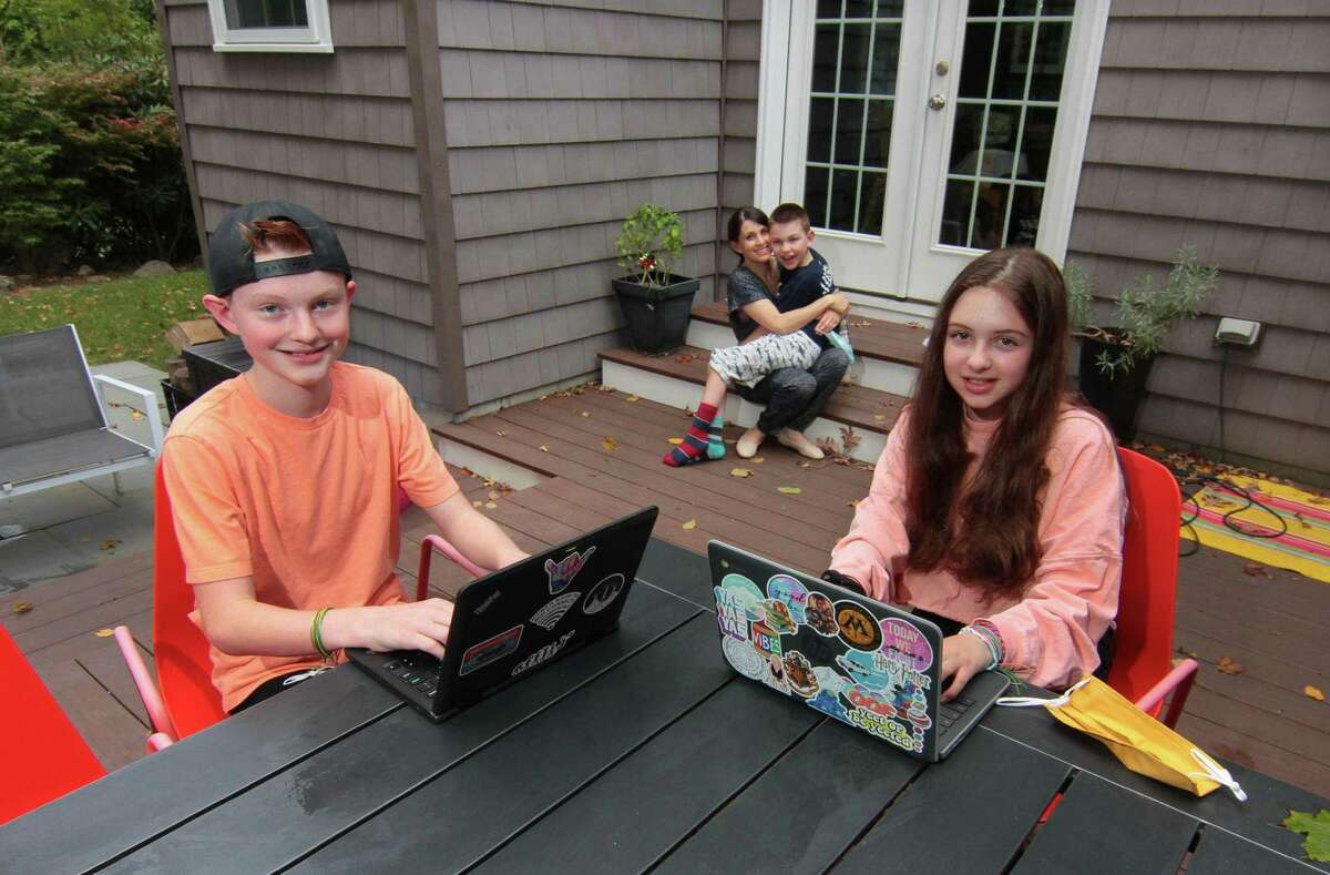 The Buck siblings, who are all remote learning, pose at their home in Greenwich, Conn., on Friday Oct. 2, 2020. From left to right is James, who is now 13 and in 7th grade; mom Allyson with Samuel, 10, in 5th grade; and Imogen, who is now 15 and in 9th grade.