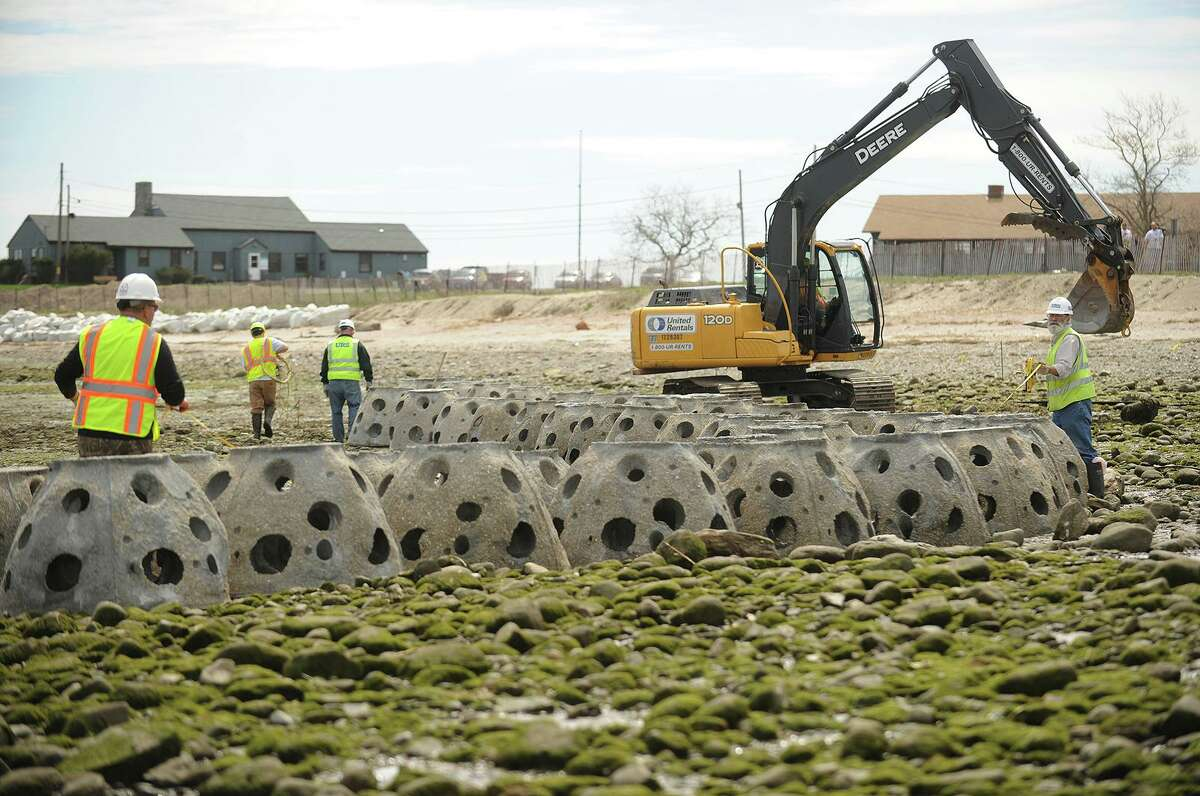 Concrete Reef Balls are guided into place during the installation of a