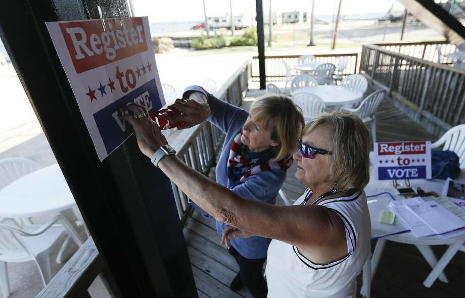 Diana Green, center, and Sharon O'Neil help set out a table for residents to register to vote during Float the Vote on Lake Conroe, Saturday, Oct. 3, 2020, in Conroe. In addition to a voter registration booth, the event included a boat parade and flyover. Photo: Jason Fochtman/Staff Photographer / 2020 © Houston Chronicle