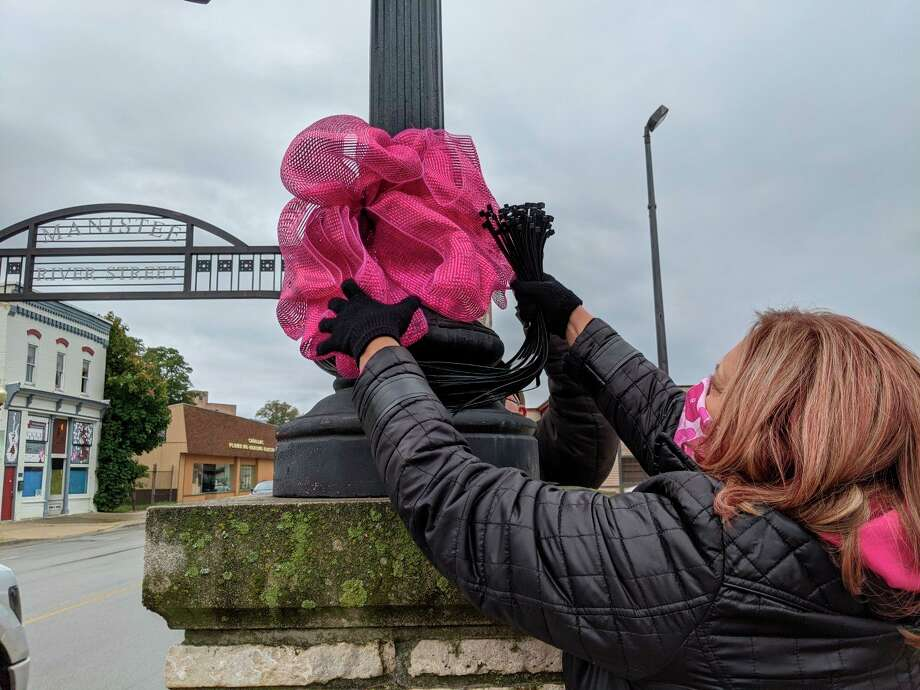 """Pink bows can now be found on River Street in Manistee after volunteers attached the bows to lamp posts and other fixtures on Saturday afternoon. The bows can be found this month during the altered Paint the Town Pink event that raises """"awareness of the importance of screenings in the fight against breast cancer.""""(Courtesy photo/Julie Mueller)"""