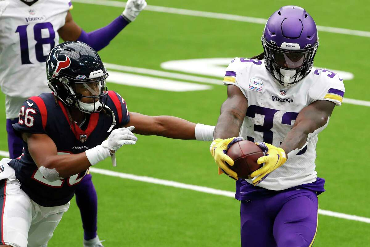 Minnesota Vikings running back Dalvin Cook (33) stretches the ball across the goal line as he runs past Houston Texans cornerback Vernon Hargreaves III (26) for a 7-yard touchdown run during the first half of an NFL football game at NRG Stadium on Sunday, Oct. 4, 2020, in Houston.