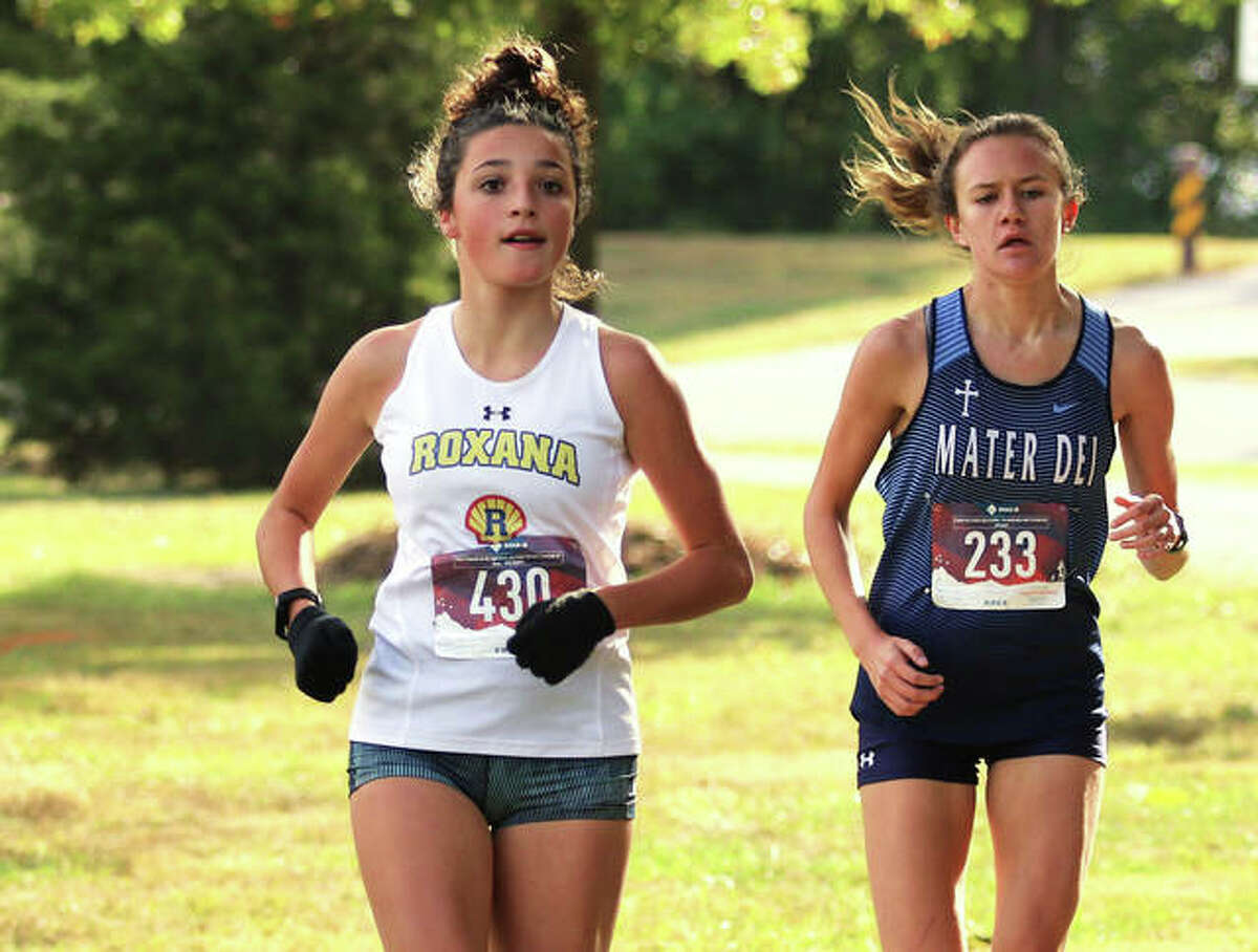 Roxana's Kendall Kamp (left) approaches the one-mile mark ahead of Breese Mater Dei's Trina Brokering in the Nos. 5-7 heat at Saturday's Alhambra Invite in Alhambra.