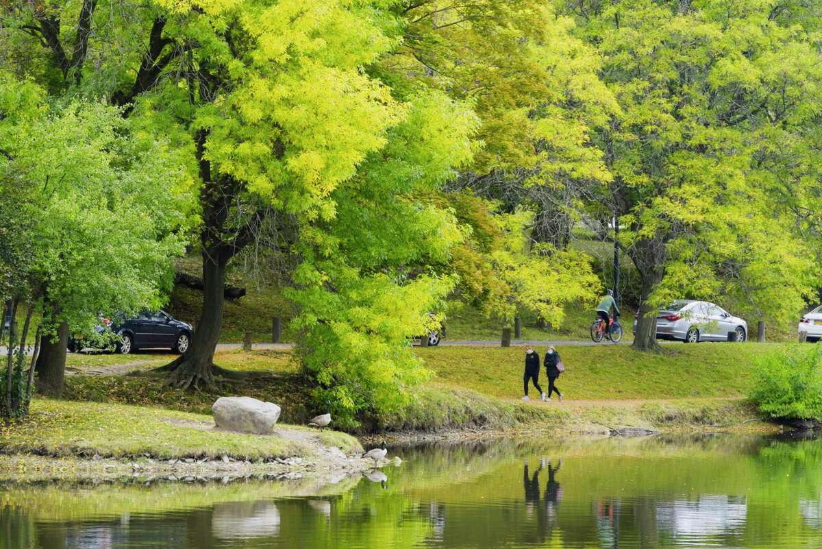 Leaves are changing color at Washington Park as people make their way around the lake on Sunday, Oct. 4, 2020, in Albany, N.Y. (Paul Buckowski/Times Union)