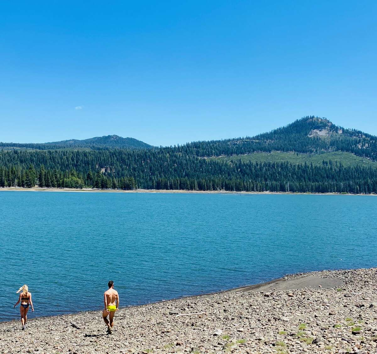 Two hikers take a dip in Snag Lake.