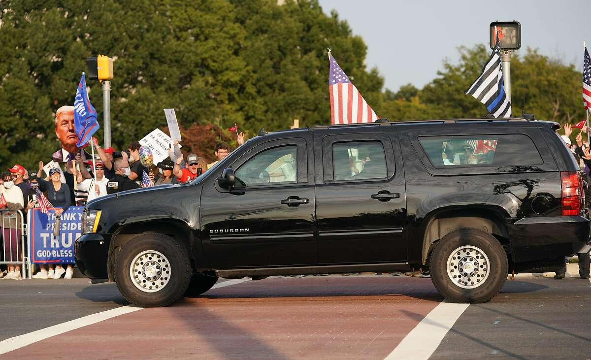 A car with US President Trump drives past supporters in a motorcade outside of Walter Reed Medical Center in Bethesda, Maryland on October 4, 2020. (Photo by ALEX EDELMAN / AFP) (Photo by ALEX EDELMAN/AFP via Getty Images)