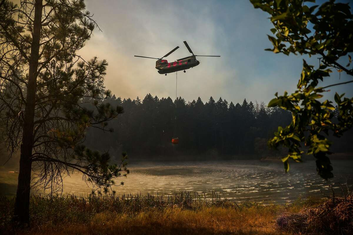 A helicopter picks up water from a pond to make drops onto the Glass Fire near Highway 29 on Sunday, Oct. 4, 2020 in Calistoga, California.