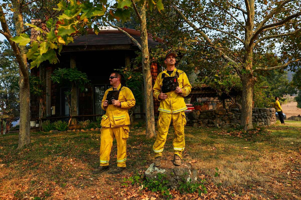 (L-r) Firefighters Dave Novelli and Scott Sousa watch a helicopter drop over the Glass Fire off of Highway 29 as they keep watch over a threatened house on Sunday, Oct. 4, 2020 in Calistoga, California.