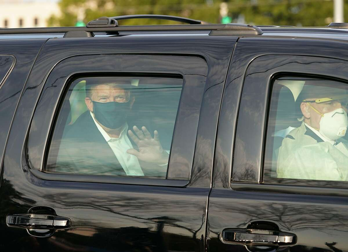 President Trump waves from the back of a car in a motorcade outside of Walter Reed Medical Center in Bethesda, Maryland on Ocotber 4, 2020.