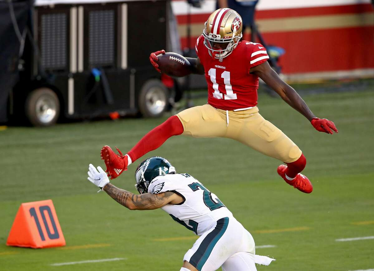SANTA CLARA, CALIFORNIA - OCTOBER 04: Brandon Aiyuk #11 of the San Francisco 49ers leaps over Darius Slay #24 of the Philadelphia Eagles to score a touchdown against the Philadelphia Eagles during the first quarter at Levi's Stadium on October 04, 2020 in Santa Clara, California. (Photo by Ezra Shaw/Getty Images)