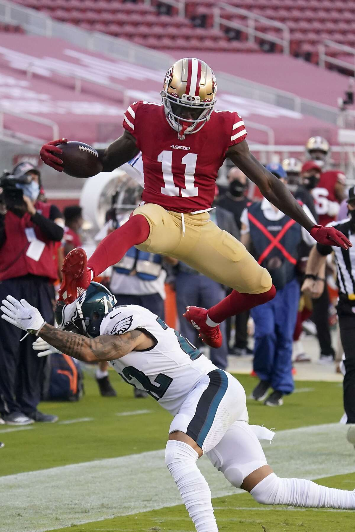 San Francisco 49ers wide receiver Brandon Aiyuk (11) jumps past Philadelphia Eagles safety Marcus Epps (22) to score a touchdown during the first half of an NFL football game in Santa Clara, Calif., Sunday, Oct. 4, 2020. (AP Photo/Tony Avelar)