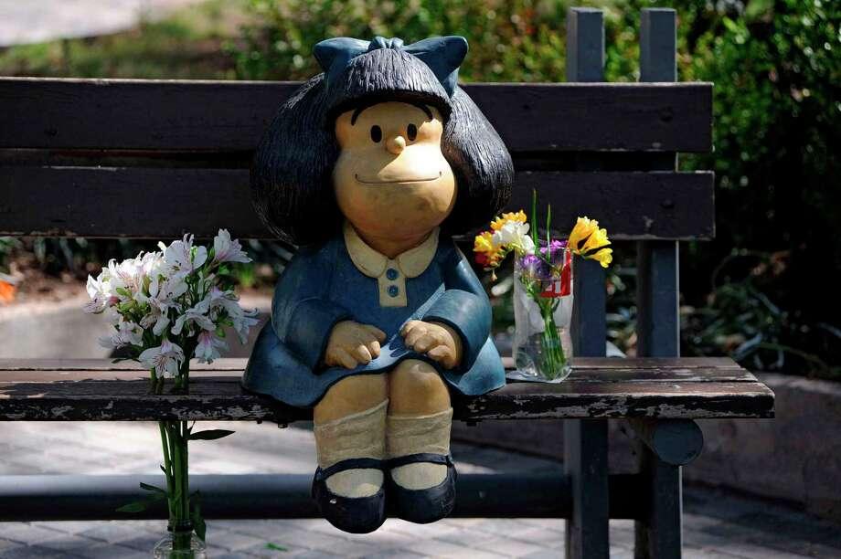 """Un ramo de flores es visto junta a una estatua de Mafalda, un personaje de caricatura creado por el caricaturista argentino Joaquín Salvador Lavado, mejor conocido como """"Quino"""", en Mendoza, Argentina, el 30 de septiembre de 2020, el día de su fallecimiento. Quino falleció ese día a la edad de 88 años. Photo: Andrés Larrovere /AFP Via Getty Images / AFP or licensors"""