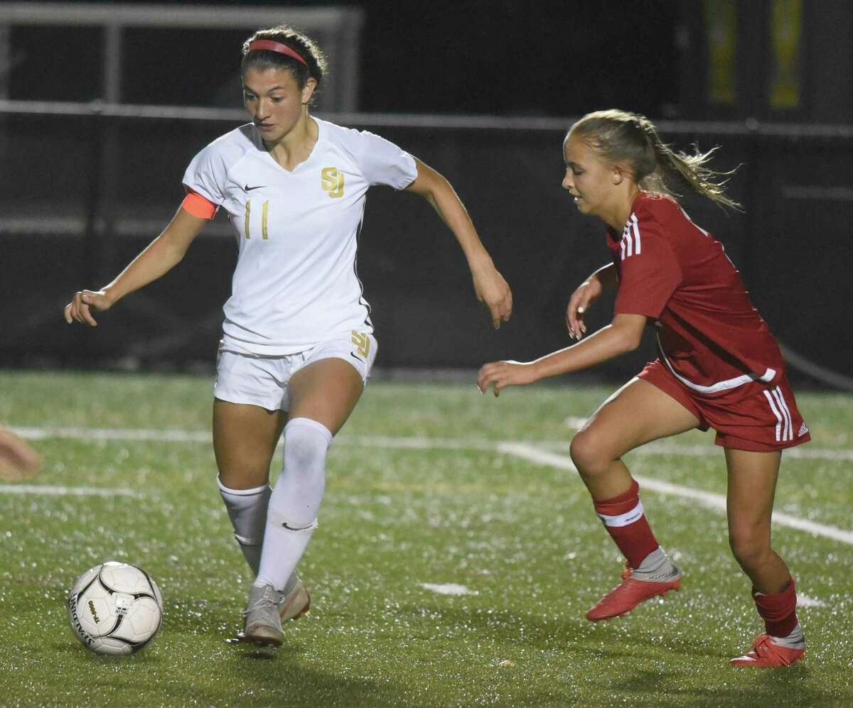 St. Joseph's Maddie Fried (11) controls the ball while New Canaan's Sophie Potter defends in during a 2019 game.
