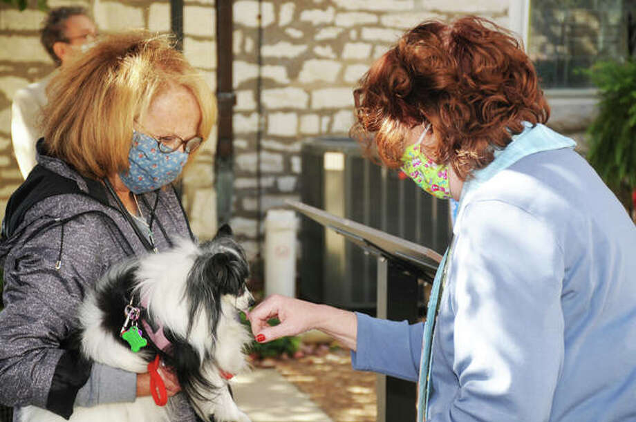 Rev. Cynthia Sever, of Alton's St. Paul's Episcopal Church, receives a thank-you from canine Cosette, held by owner Donna Taylor, at the church's annual Blessing of the Animals service Sunday.