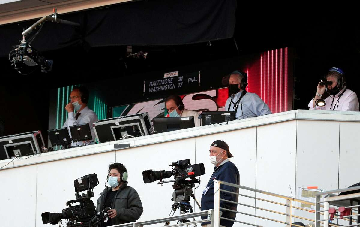 The broadcast crew - including Chris Collingsworth at left and Al Michael, center, all masked up in the booth in the first half as the San Francisco 49ers played the Philadelphia Eagles at Levi's Stadium in Santa Clara, Calif., on Sunday, October 4, 2020.