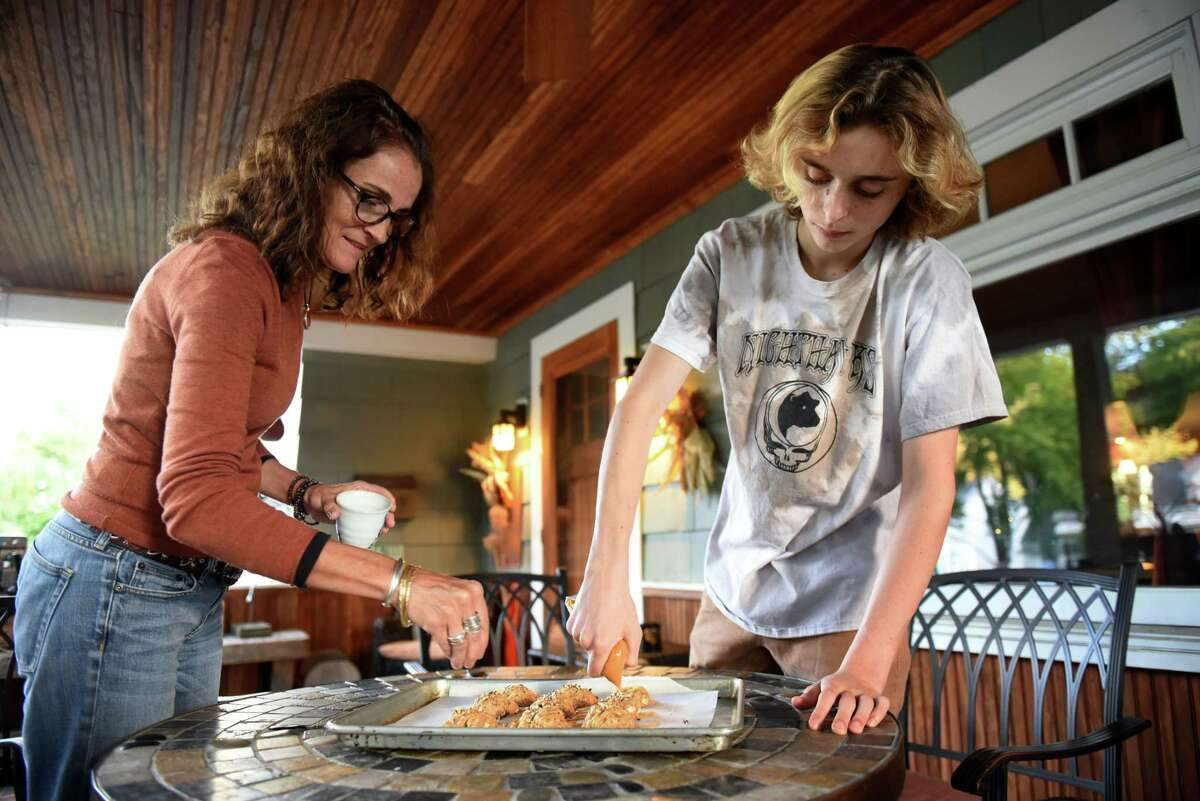 Caroline Barrett is assisted by her son, Eliot, as the pair put the finishing touches on a batch of apple and oatmeal cookies with warm spice and pecans on Thursday, Oct. 1, 2020, in Delmar, N.Y. (Will Waldron/Times Union)