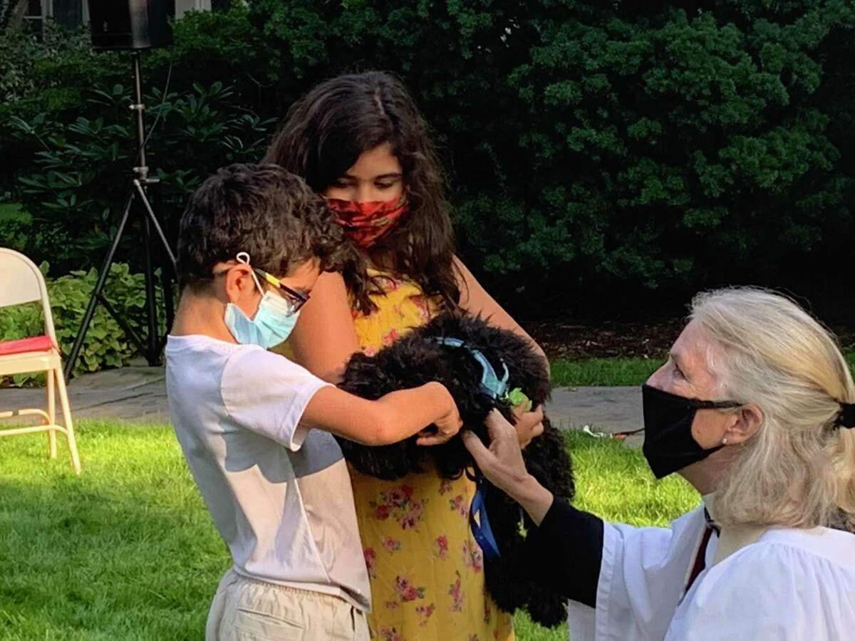 Dante and Mila Rotondi hold 5-month-old Obi Wan as the Rev. Peggy Hodgkins blesses the puppy during the Blessing of the Animals, held outside Trinity Episcopal Church in Southport Sunday, Oct. 4.