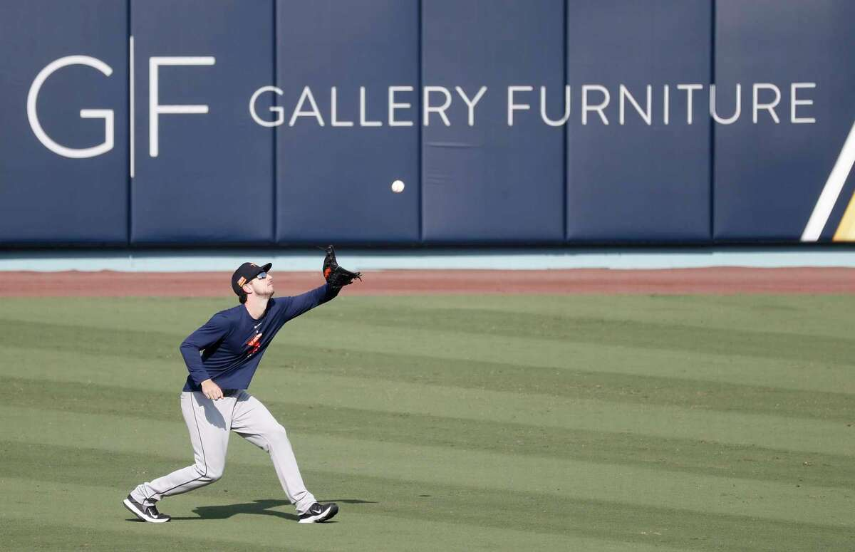 Houston Astros left fielder Kyle Tucker catches a fly ball, with Gallery Furniture's ad on the outfield fence, during batting practice and workouts, Sunday, October 4, 2020, in Los Angeles, as the Astros prepared to take on the Oakland Athletics in Game 1 of the ALDS, Monday, at Dodger Stadium.