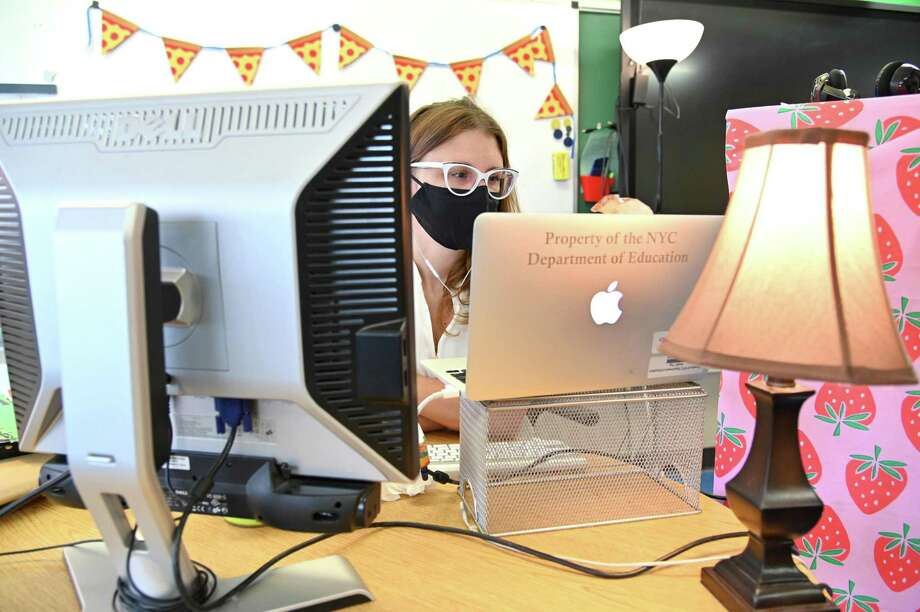 A teacher wears a mask and teaches remotely from her classroom in New York City last month. Photo: Michael Loccisano / TNS File Photo / Getty Images North America