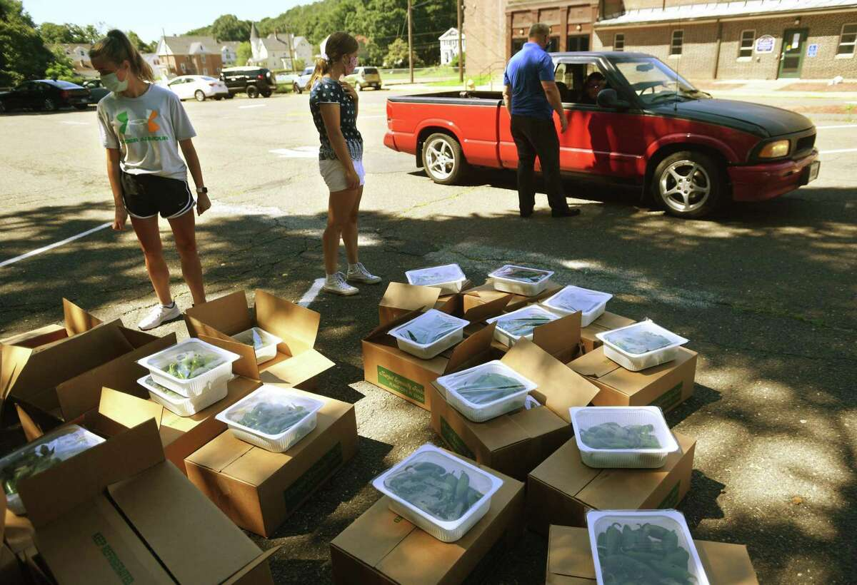 Boxes of free fresh produce are brought to waiting cars during a Farmers to Families food distribution outside the Seymour Community Center in Seymour, Conn. on Monday, August 3, 2020. Boxes containing nearly 24 pounds of vegetables, meat and diary will be distributed Oct. 6 from noon to 6:30 p.m. at Ansonia's Nolan Field.