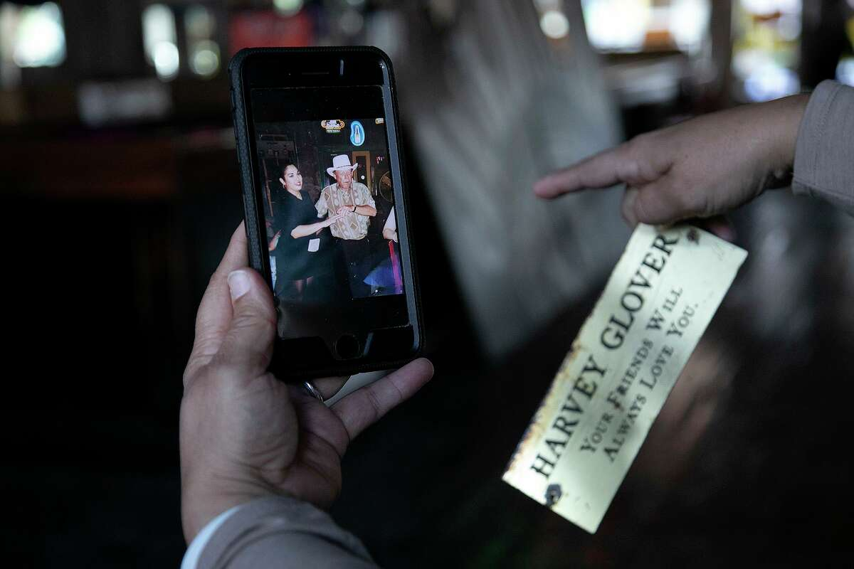 Brenda Cordoway-Martinez, who was a bartender at Cadillac Bar for close to 10 years shows a photo of herself dancing with long-time customer, Harvey Glover. She's pointing to the place in the bar they were dancing as she holds the name plate that was affixed to the bar in his memory.
