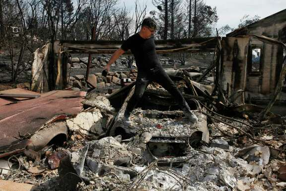 Boback Emad climbs across one of his destroyed cars to take photographs for his insurance company while surveying the destruction of his home for the first time in the Fountaingrove neighborhood of Santa Rosa on Oct. 17, 2017.