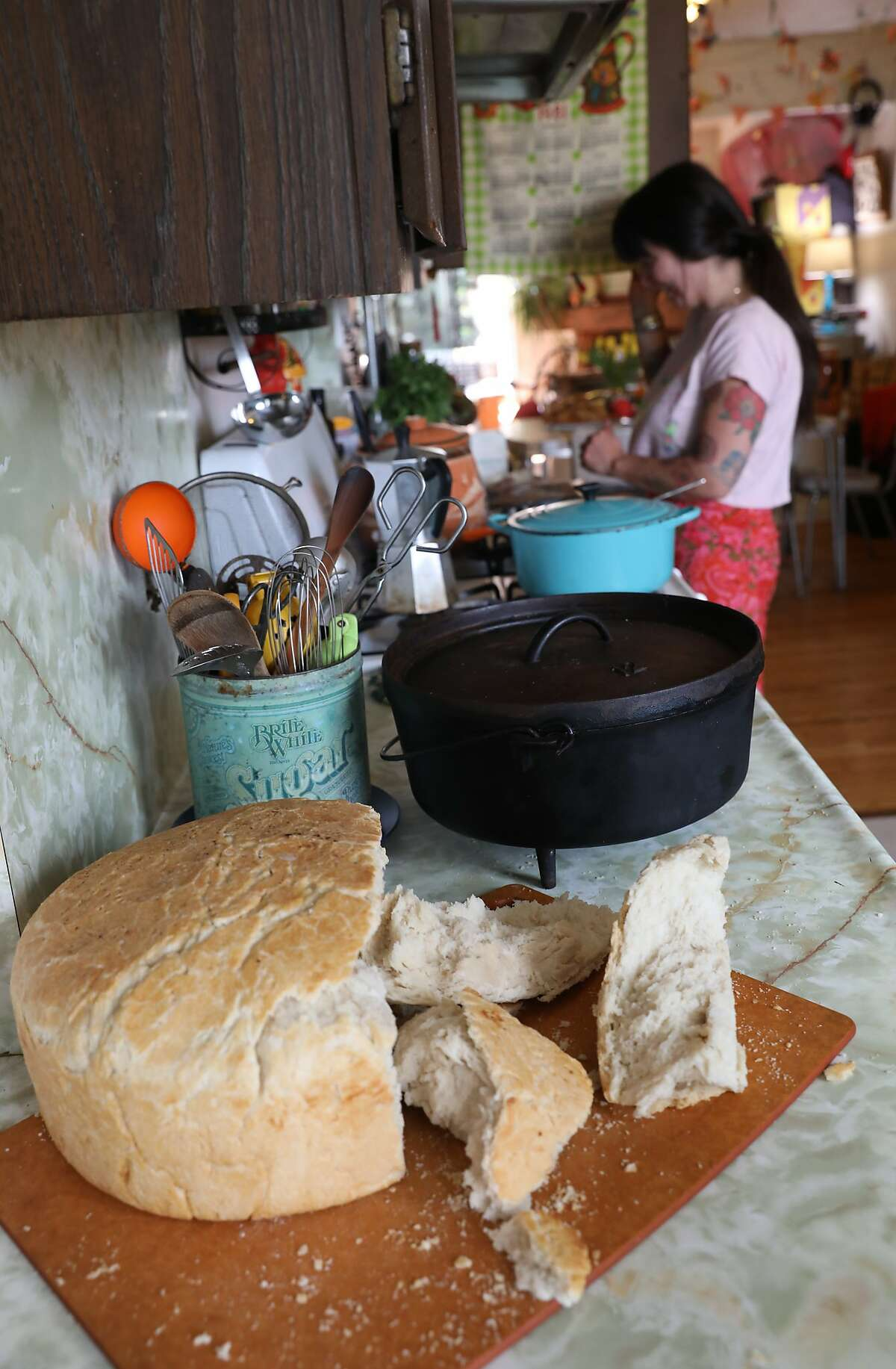 Vannessa Gonzalez cooks food for her dad's retirement party as a loaf of handmade Basque bread sits on the counter of her Sunset District home.