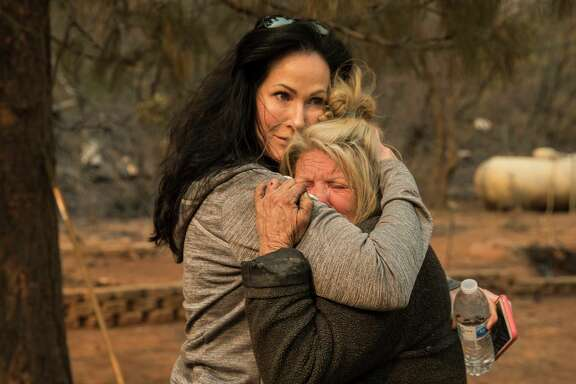 Animal volunteer evacuator Tamara Houston (left,) comforts Cathy Fallon, who survived the Camp Fire while hunkering down in her home on Edgewood Laned in Paradise (Butte County).
